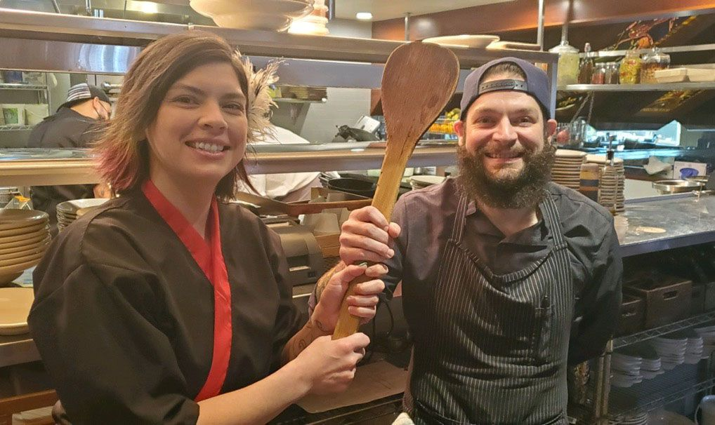 Chef Suki Otsuki passes the chef spoon to Josh Bonee, the new executive chef at Meddlesome Moth. Otsuki has resigned her position and is working as a chef at a yoga retreat in east Texas.