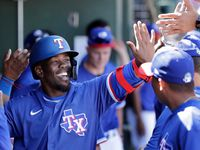 Texas Rangers' Adolis Garcia is congratulated in the dugout after hitting a solo home run against the Arizona Diamondbacks in the third inning during a spring training baseball game Thursday, March 5, 2020, in Surprise, Ariz.