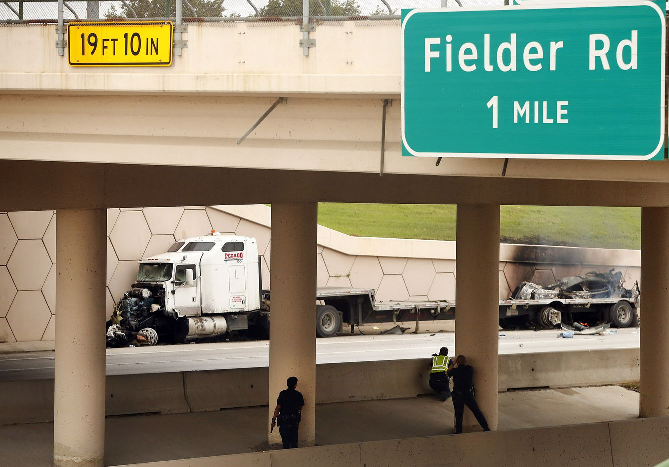 Police officers draw their guns on a semi truck after it wrecked following a high speed chase on Interstate 30 at Cooper St. in Arlington  Friday, June 9, 2017. A vehicle alongside the semi was pinned up against the wall and burned. (Tom Fox/The Dallas Morning News)