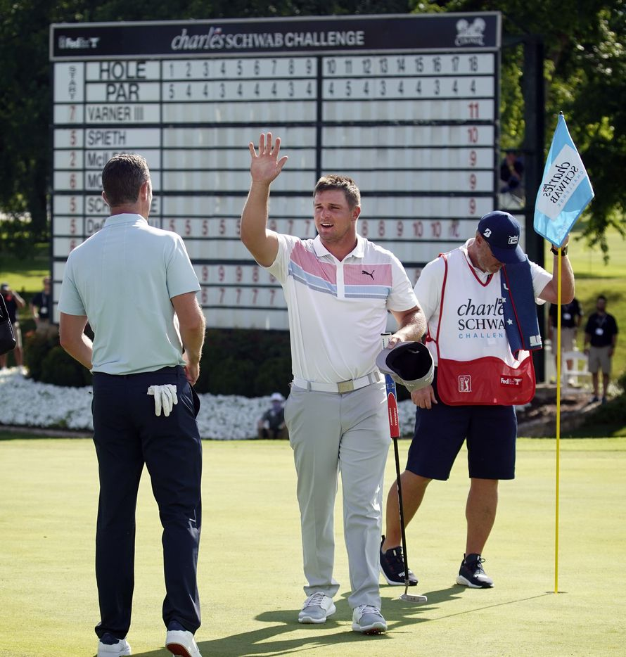 PGA Tour golfer Bryson DeChambeau gives an air high-five to playing partner Justin Rose after their second round of the Charles Schwab Challenge at the Colonial Country Club in Fort Worth, Friday, June 12, 2020.  DeChambeau finished the day tied for second with Jordan Spieth. The Challenge is the first tour event since the COVID-19 pandemic began. (Tom Fox/The Dallas Morning News)