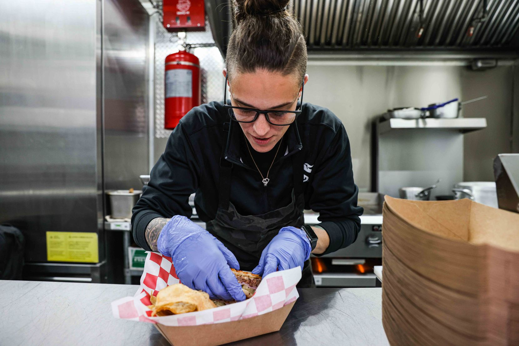 Chef Jordan Savell prepares El Cubano, her signature cuban sandwich with smoked pork shoulder, ham, swiss cheese, chef J's pickles, horseradish mustard and cuban bread in her food truck Bullfish Foods in Fort Worth on Wednesday, March 24, 2021.