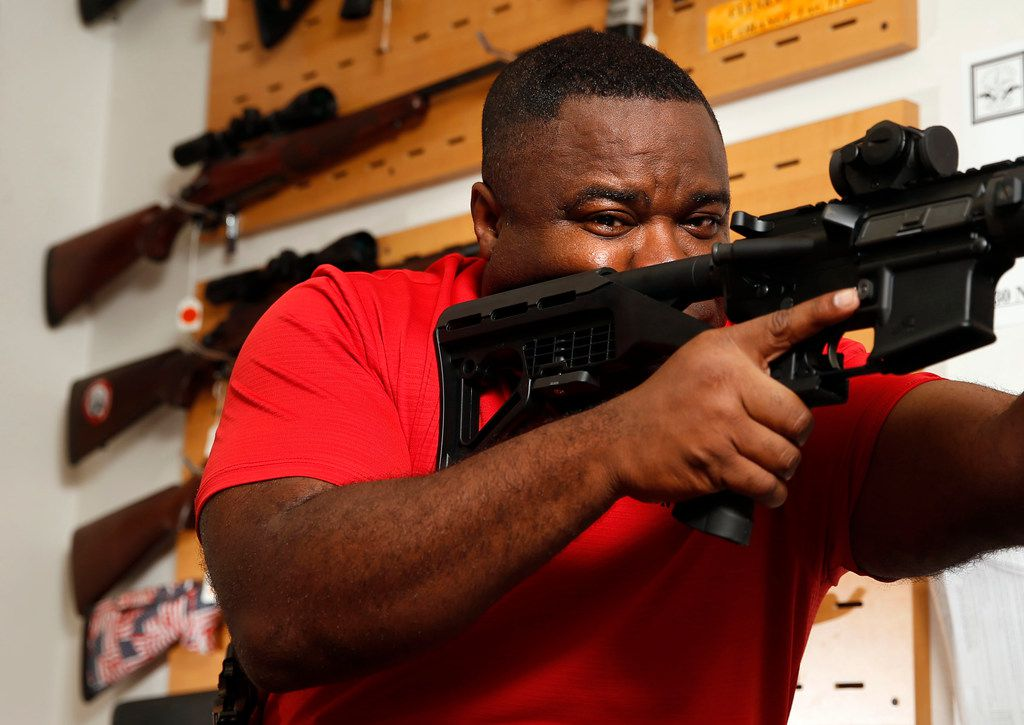 Michael Cargill, Central Texas Gun Works owner poses with an AR-15 with a bump stock attached in his store in Austin, Texas on Thursday, October 19, 2017.