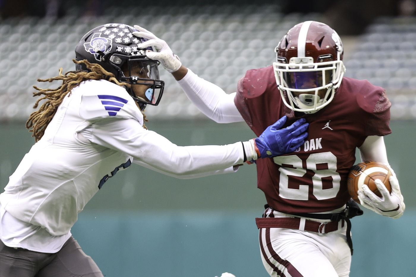 Red Oak running back Iverson Young (28) gives a stiff-arm to Mansfield Summit defensive back Sean Smith (5) during the first half at Globe Life Park in Arlington, Texas, Friday, Jan. 1, 2021. (Elias Valverde II / Special Contributor)