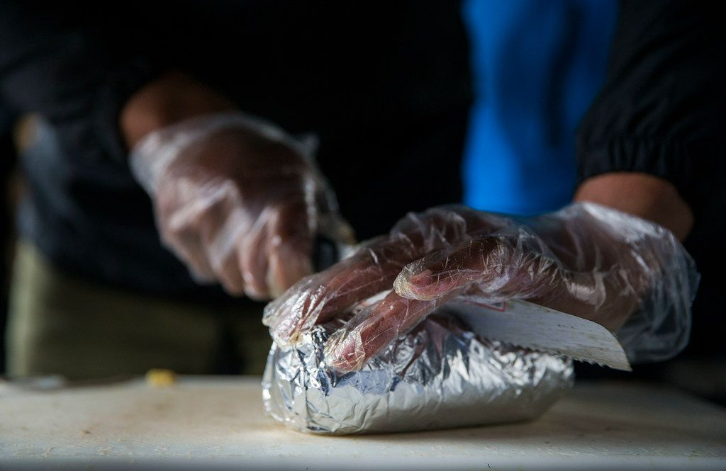 "Jessie Washington, Brunchaholics owner and chef, cuts a ""Soul Food Burrito"" in half at his company's booth at the Dallas Farmers Market in Dallas on Saturday, March 30, 2019. Washington said he created the burrito as a joke, but people saw it on his social media account and wanted try it so he started to sell them. (Daniel Carde/The Dallas Morning News)"
