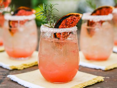 Texas Greyhound, in a rocks glass, rimmed with pink sea salt, garnished  with broiled grapefruit slice and rosemary