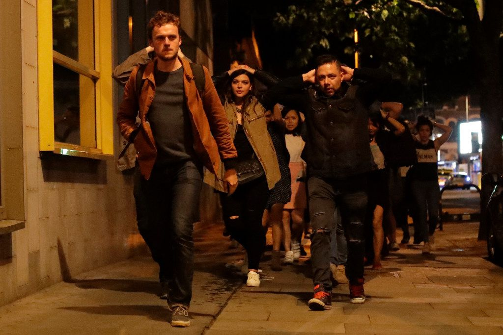 People with their hands on their heads about 10 minutes after midnight as they leave from inside a police cordon after an attack in London, Sunday, June 4, 2017.