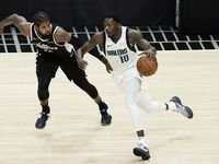 Dallas Mavericks forward Dorian Finney-Smith brings the ball up the floor past LA Clippers guard Paul George during the second half of a playoff game at Staples Center in Los Angeles on May 22, 2021.