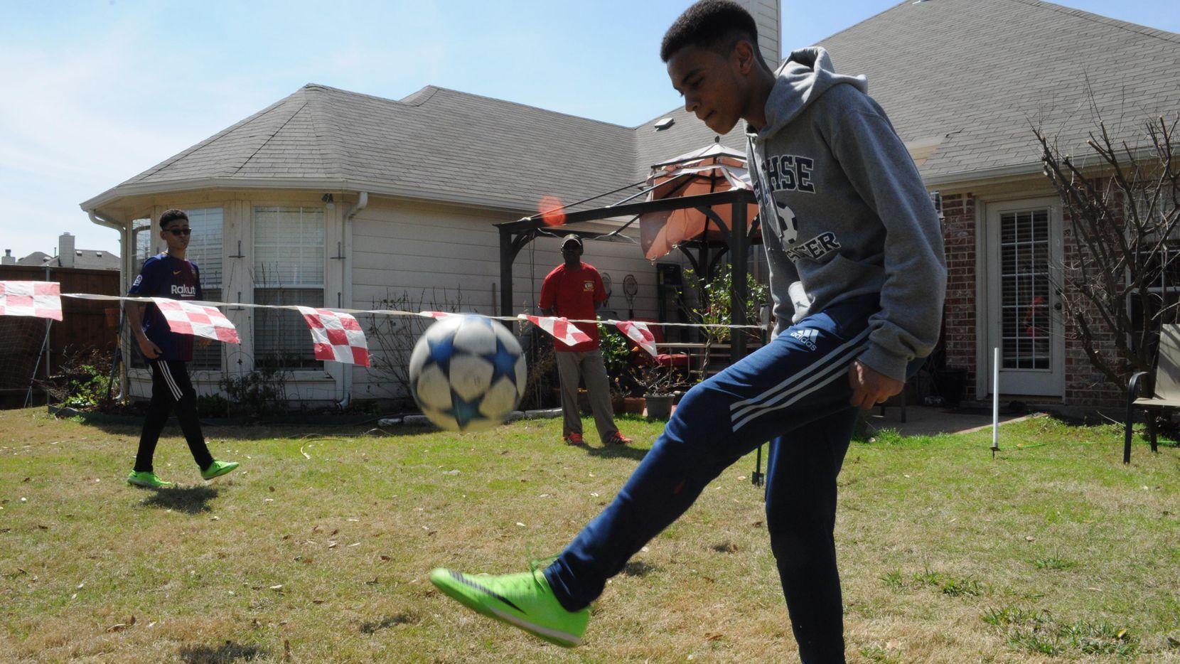 Miguel Kobby Adoboe entrena con un balón de futbol en el patio de su casa en Sachse, Texas, junto a su hermano Jojo y su papá Ferdie.(JAVIER GIRIBET/ESPECIAL PARA AL DÍA)