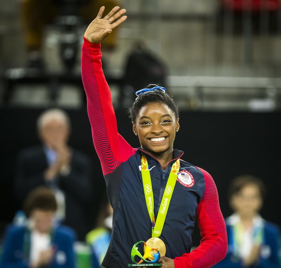 Simone Biles of the United States waves to the crowd after receiving her gold medal for the women's gymnastics all-around final at the Rio 2016 Olympic Games on Thursday, Aug. 11, 2016, in Rio de Janeiro.  Aly Raisman took silver.