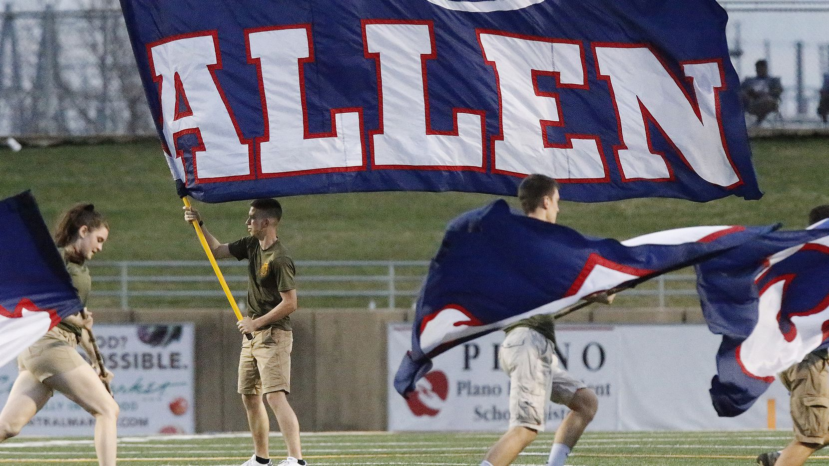 Aidan McGlothlin, 16, with the Allen High School Marine Core JROTC waves an Allen flag after a touchdown during the first half as Plano High School hosted Allen High School in a District 9-6A football game at Clark Stadium in Plano in 2019.