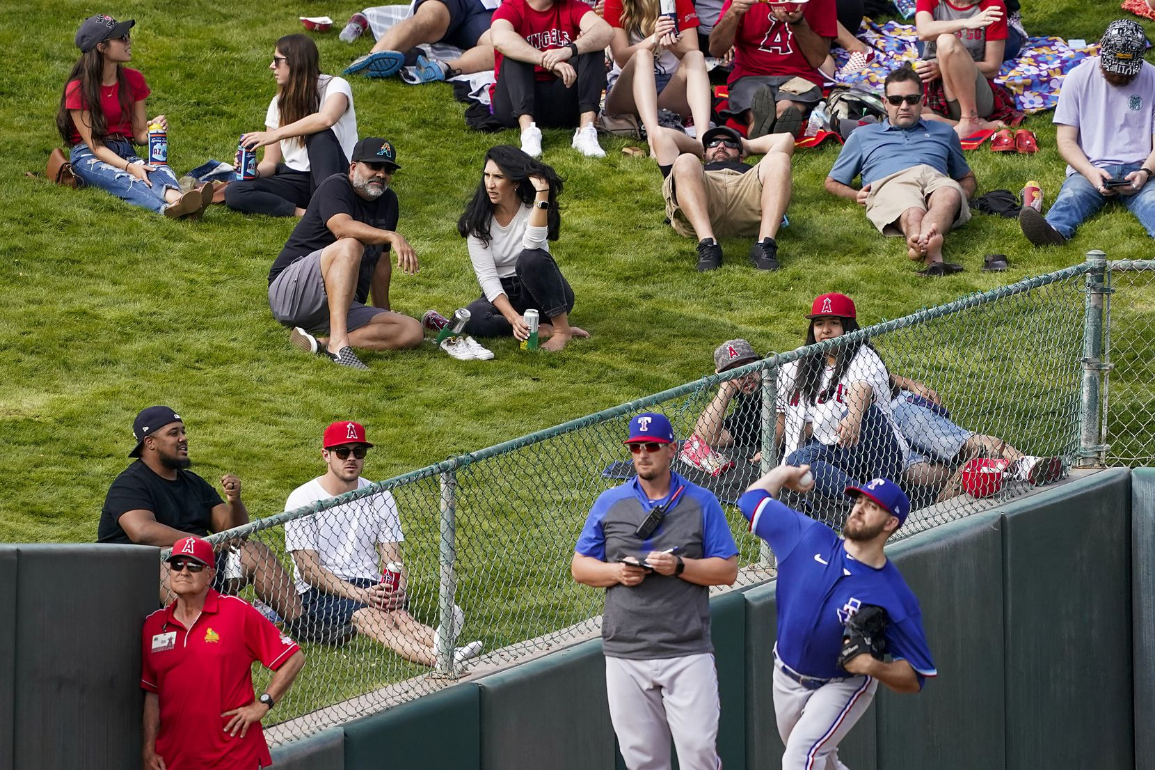 Fans on the outfield berm watch Texas Rangers pitcher Lake Lemoine warm up in the  bullpen during the sixth inning of a spring training game at Tempe Diablo Stadium on Friday, Feb. 28, 2020, in Tempe, Ariz.