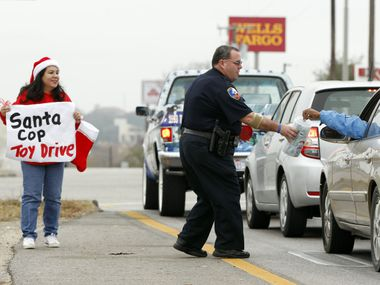 Two of Santa's helpers, Gaby Hinojosa and the Duncanville Police Department's Doug Sisk, collected donations of toys and cash Saturday to provide Christmas for children in need.