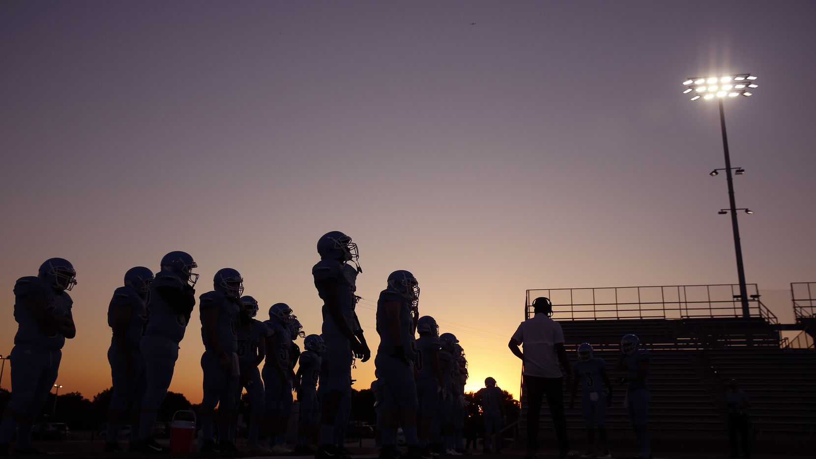 general football coronavirus  As the sun sets behind Loos Stadium, the Thomas Jefferson football team waits to take the field against Pinkston in Addison, Texas, Thursday, October 1, 2020. This is the first Dallas ISD game of the season. (Tom Fox/The Dallas Morning News)