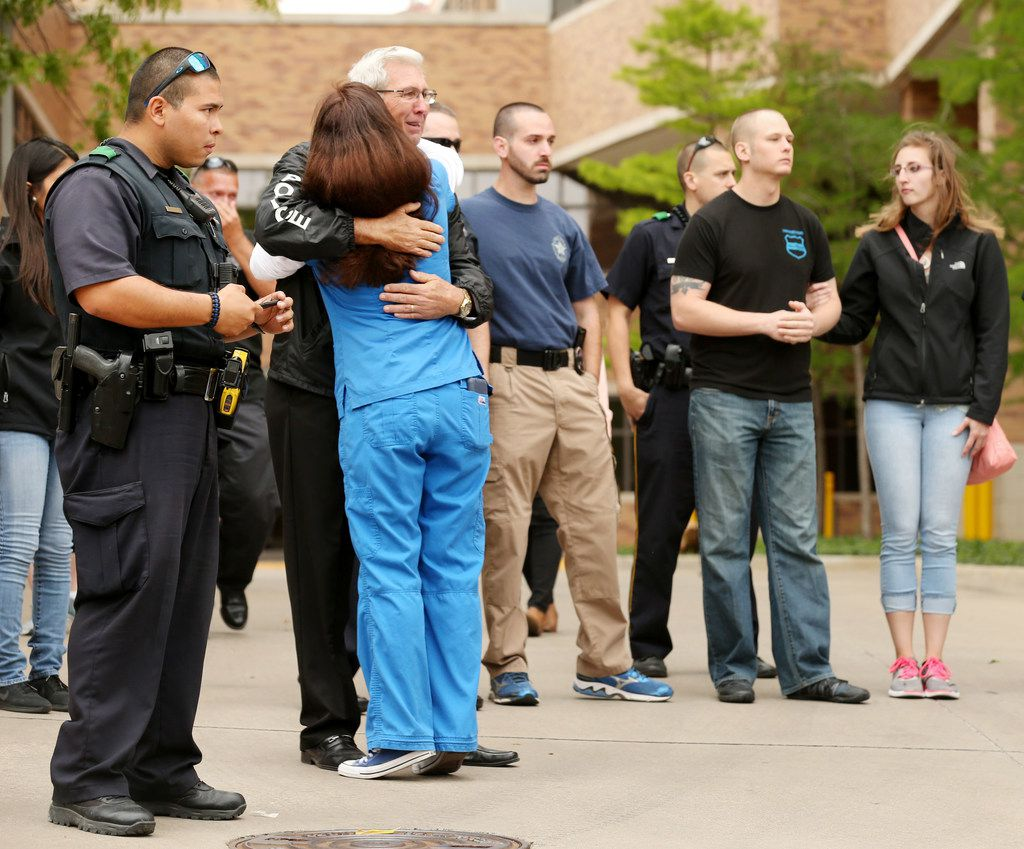 Steve Ledbetter (third from left), a retired Dallas police officer of 40 years, embraces a mourner as Dallas police department members and hospital personnel meet outside Texas Health Presbyterian Hospital of Dallas in a showing of support Wednesday April 25, 2018. Dallas police chief U. Renee Hall announced that officer Rogelio Santander died this morning after he and another Dallas police officer, along with a loss prevention officer, were shot yesterday at a Home Depot on the 11600 block of Forest Central Drive. (Andy Jacobsohn/The Dallas Morning News)