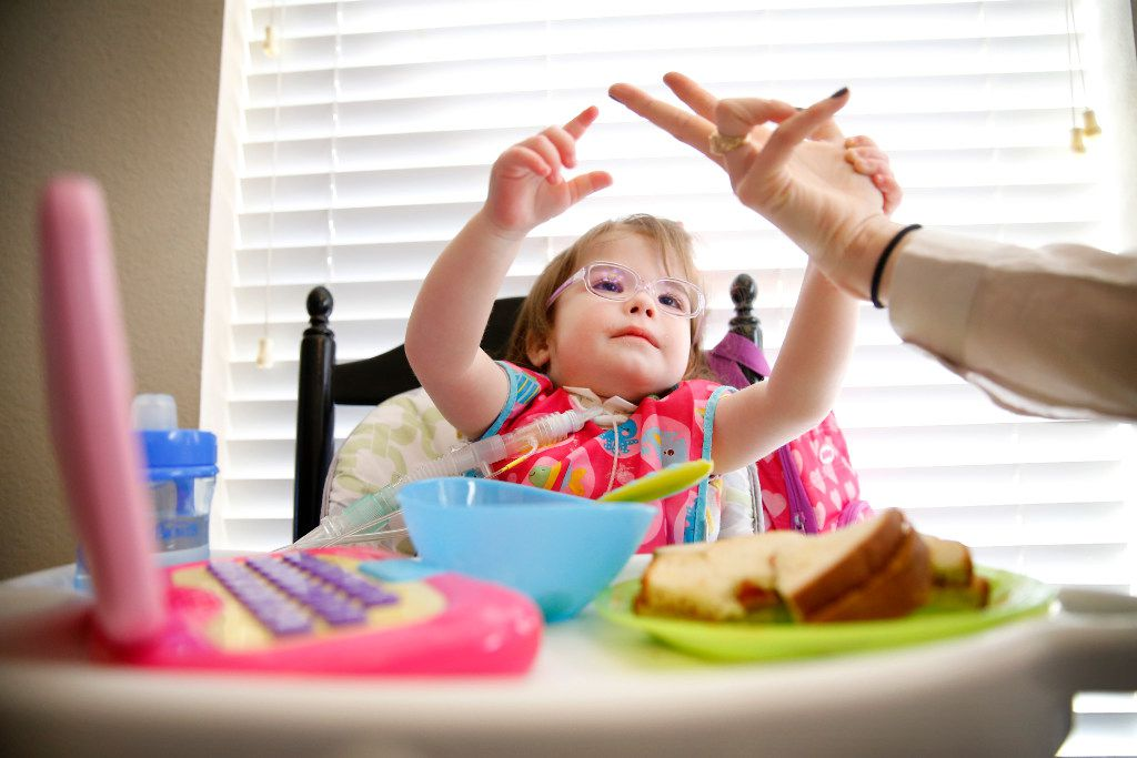 Natalie Gregory shows her 2 year-old daughter Christina  how to count as she eats her lunch, Tuesday, January 31, 2017.  Christina suffers from CCHS (Congenital Central Hypoventilation Syndrome), a genetic disorder that affects her breathing. While she eats, there is a ventilator unit that hooks up to a trachea tube in her neck to assist in breathing when needed.  The Gregory's have two pediatric nurses that keep a watchful eye on Christina at their Southlake,Texas home. The Gregorys are affected by Texas' change to their Medicare healthcare coverage, switching to a MCO plan from an HMO plan, limiting their care to within the region -a cumbersome issue for families dealing with 24/7 care. (Tom Fox/The Dallas Morning News)
