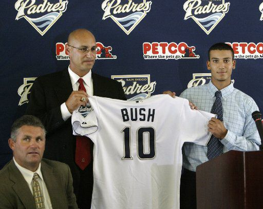 San Diego Padres director of scouting, Bill Gayton, and the teams' number one draft choice, Matt Bush, right, hold up Bush's new Padres' jersey as general manager Kevin Towers, left, looks on at a news conference in this June 7, 2004 file photo in San Diego. Bush, the top pick in the baseball draft two weeks ago, was suspended indefinitely by the San Diego Padres on Monday, June 21 a day after he was arrested at a bar in Peoria, Ariz.. (AP Photo/Lenny Ignelzi)