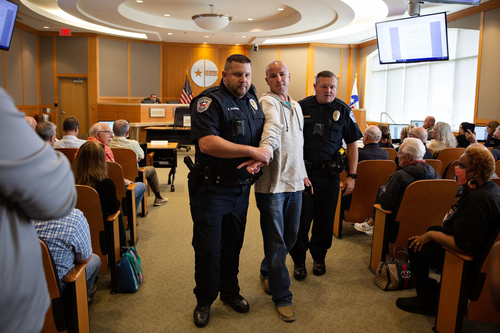 Joshua Murray is escorted out of the Collin County Commissioners Court meeting by police after being ruled in contempt.