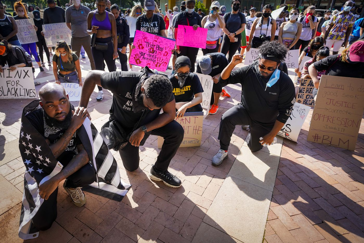 Jacob Clayton (left) kneels for a moment of silence with Brandon Moore during a protest on Thursday, June 4, 2020, in Addison. Protests continued Thursday in the response to the death of George Floyd.