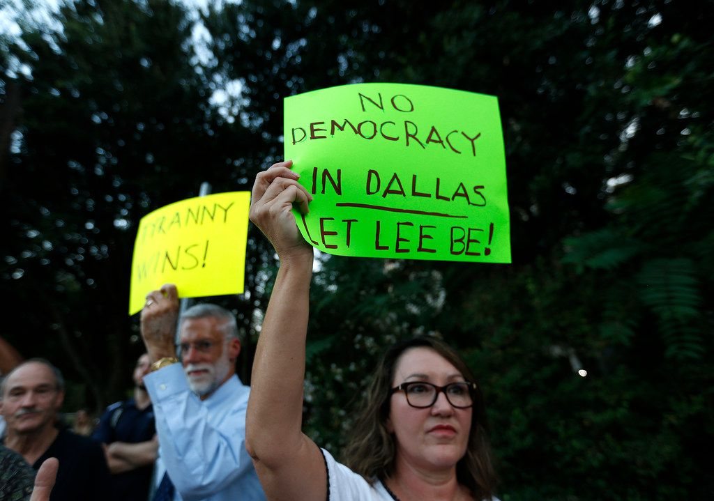 Lisa Grasso, right, and her husband Randy Grasso hold up signs while crew members work to remove the Robert E. Lee statue at Robert E. Lee Park in Dallas, Thursday, Sept. 14, 2017. Crews arranged by Dallas officials removed the statue from its pedestal Thursday and carted it away from the park.