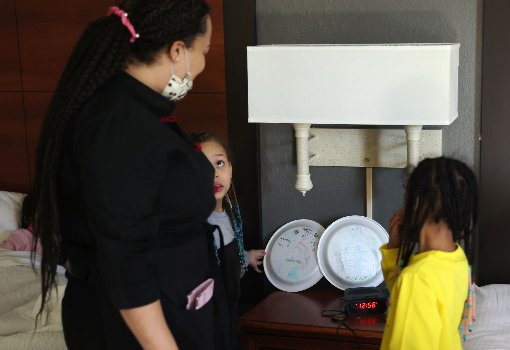 Yannoj Young, 8 (second from left) and Courtney Young, 7, (right) place their artwork on the nightstand as their mother Jonnay Mckinley watches inside their hotel room on Monday, February 1, 2021.