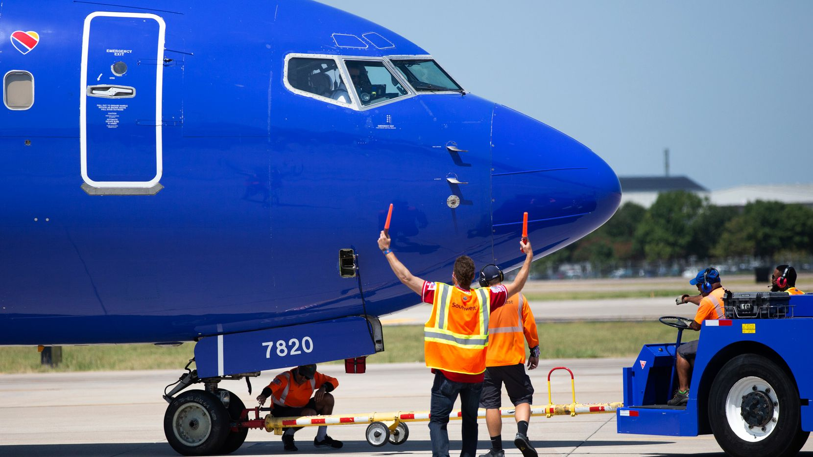 Texas Rangers right fielder Hunter Pence (center) assists aircraft marshallers as center fielder Delino DeShields Jr. (far right) accompanies a ramp agent maneuvering a plane at Dallas Love Field Airport on Tuesday, July 30, 2019. Players visited Southwest Airlines' home airport to assist with greeting customers, boarding flights and helping to ensure an on-time departure.