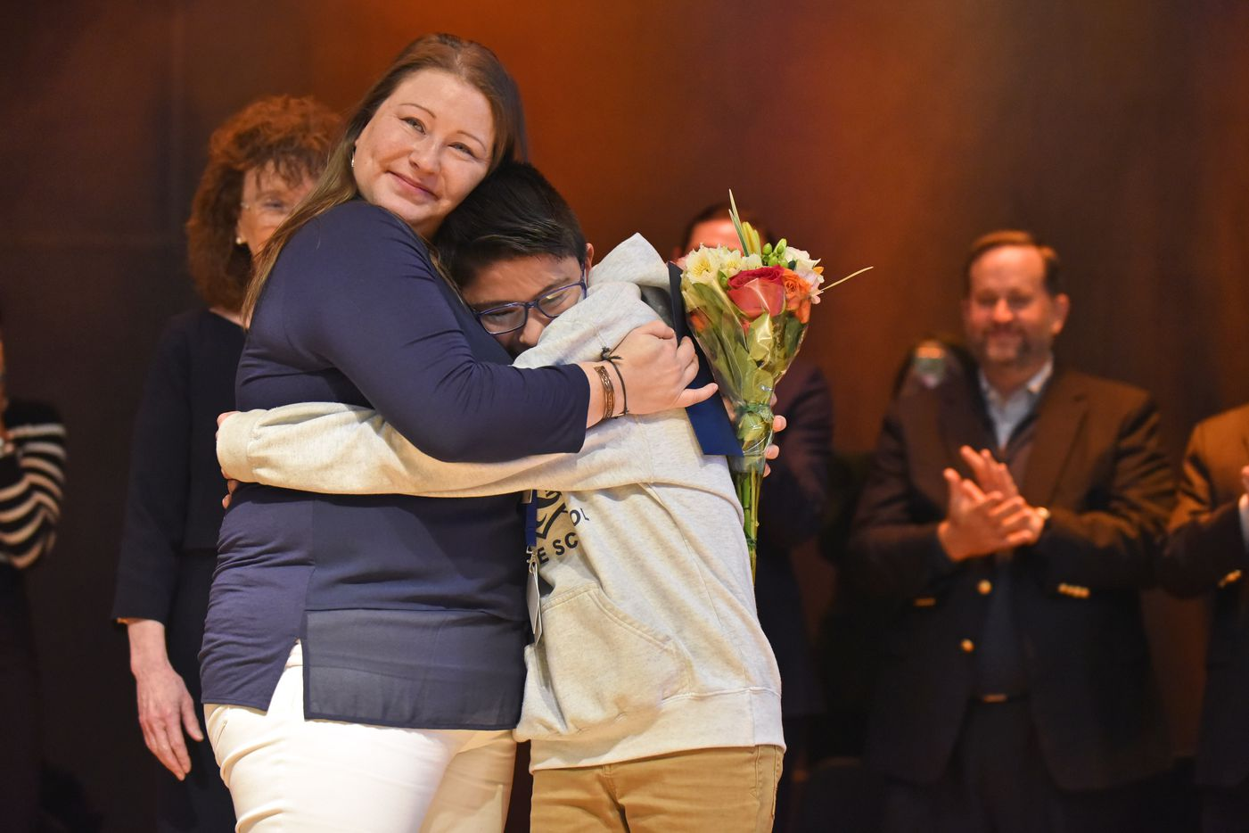 Susan Moreno, a J.L. Long Middle School Spanish teacher, hugs her son DeAngelo Moreno, 11, after she received a bouquet of flowers after being named the 2019 Milken Educator Award winner, presented by the Milken Family Foundation, at J.L. Long Middle School in Dallas, Nov. 14, 2019. The outstanding teacher award came with a $25,000 check. Ben Torres/Special Contributor