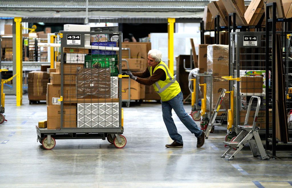 A worker moves merchandise at the Amazon fulfillment center in Aurora, Colo. The million-square-foot facility, employing 1,000 full time employees,  has over 2 million products ready to ship to customers globally.