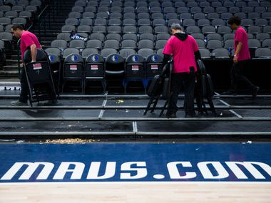 Crews remove chairs from the court after the Dallas Mavericks beat the Denver Nuggets 113-97 on Wednesday, March 11, 2020 at American Airlines Center in Dallas. During the game, the NBA suspended all games due to the spread of the new coronavirus.