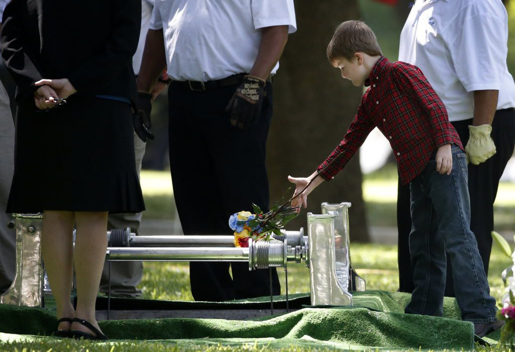 Magnus Ahrens, the 8-year-old son of Dallas Officer Lorne Ahrens, drops flowers into his father's grave on July 13, six days after he was slain in downtown Dallas.