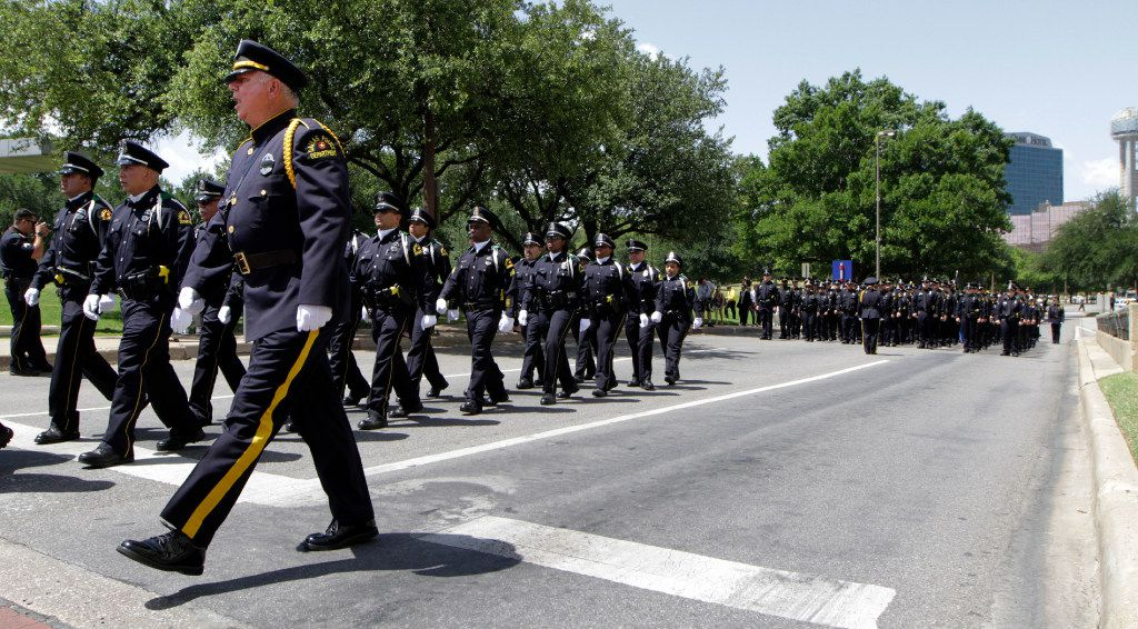 Dallas police officers march up Young St. to the annual Dallas Police Memorial Service,