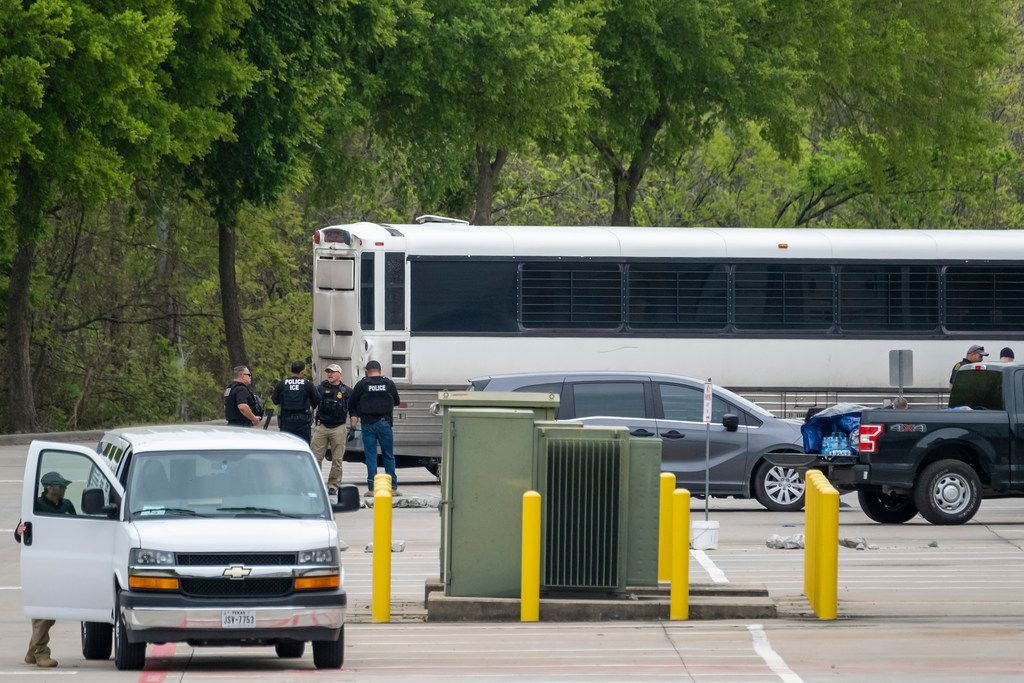 U.S. Immigration and Customs Enforcement officials were seen leading detained people to buses.