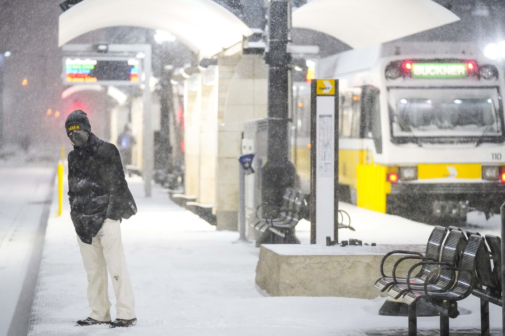 Victor Escamilla looks down the tracks as people wait in driving snow at the Pearl/Arts District station as a winter storm brings snow and freezing temperatures to North Texas on Sunday, Feb. 14, 2021, in Dallas.  DART suspended all rail operations Sunday night.