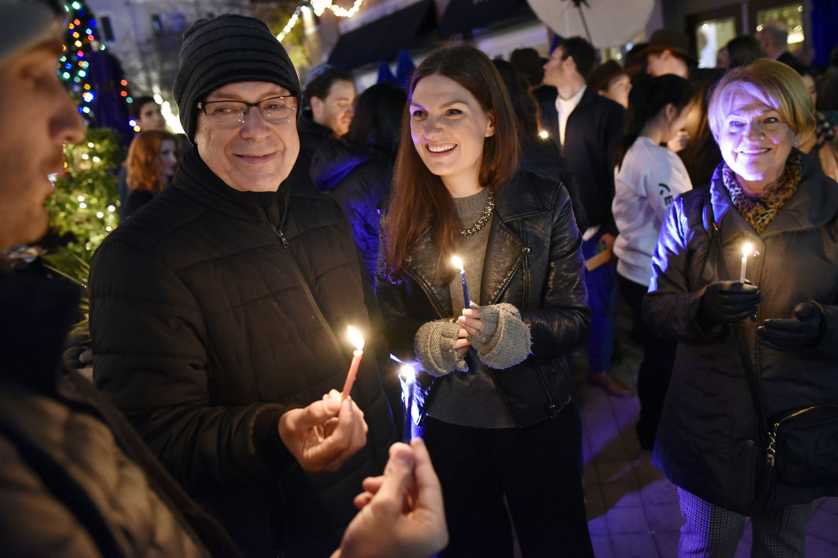 Henry and Georgia Grantham (center) held Hanukkah candles with family members Mark Jenkins (left) and Anna Grantham (right) during 2018's West Village menorah lighting hosted by the Intown Chabad. This year, Intown Chabad will host menorah lightings at Klyde Warren Park.