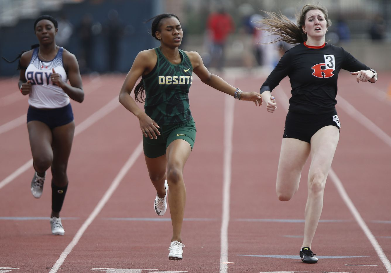 Amelliah Bireow (center), finished first in her heat for DeSotto High School during the Jesuit-Sheaner Relays held at Jesuit College Preparatory School in Dallas on Saturday, March 27, 2021.  (Stewart F. House/Special Contributor)