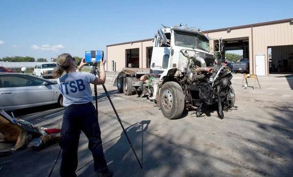 NTSB investigator Kristin Poland makes a laser scan of the truck that collided with a bus Friday night on I-35.