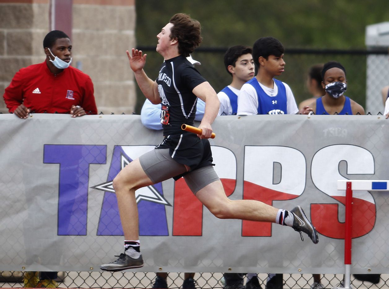A sprinter races past a TAPPS sign during a relay event. The running finals from the TAPPS state track meet were held at Waco Midway's Panther Stadium in Hewitt on May 1, 2021. (Steve Hamm/ Special Contributor)