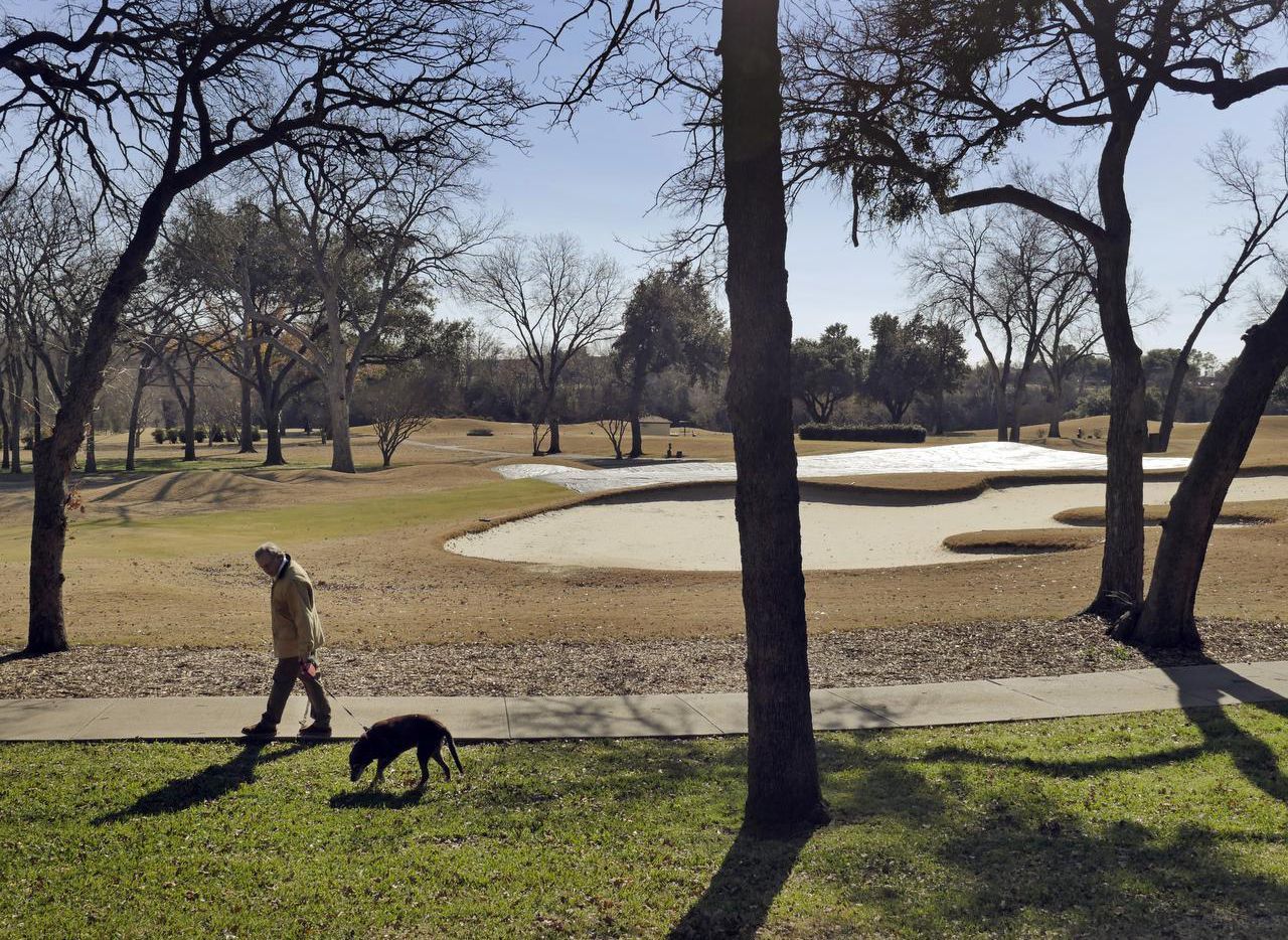 Bryan Arnold walks Josie on the half-century-old Great Southwest Golf Club, which has been sold for redevelopment. The land is zoned for light industrial use.