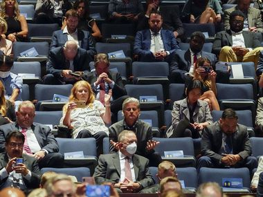 In a upper level of seating, social distancing cards are visible on unused chairs as people in the audience pray during a roundtable conversation about race relations and policing at Gateway Church Dallas Campus on Thursday in Dallas. Most of the seats lower down and closer to the stage were filled with attendees sitting side by side.