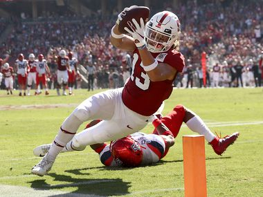 Simi Fehoko #13 of the Stanford Cardinal dives in the a touchdown after getting past Xavier Bell #37 of the Arizona Wildcats at Stanford Stadium on October 26, 2019 in Palo Alto, California.