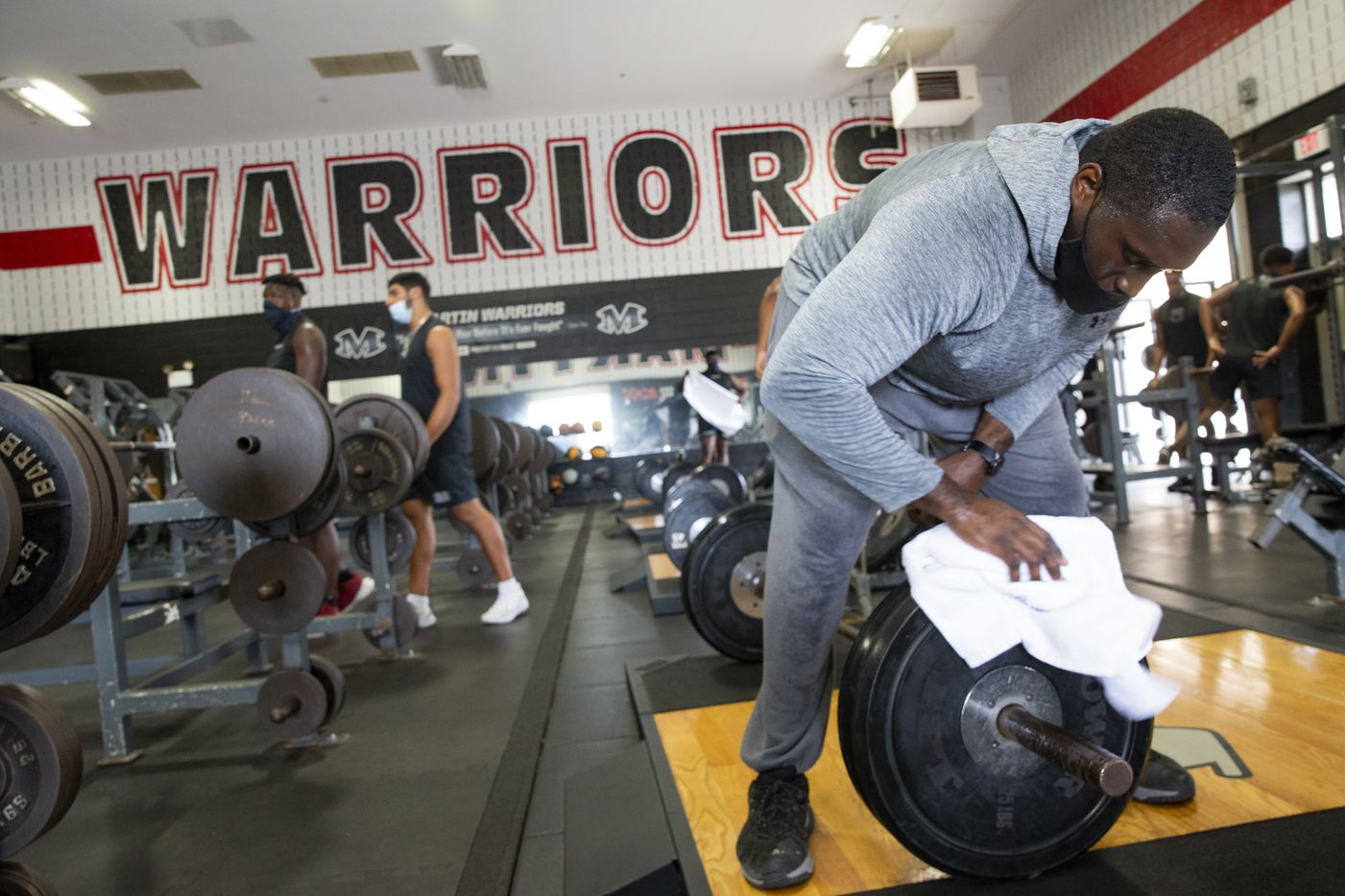 "Homicide Sergeant Brian Jones from the Arlington Police Department sanitizes equipment after working out with Arlington Martin football players at their gym as part of the ""Coach 5-0"" program on Monday, Sept. 21, 2020 in Arlington. (Juan Figueroa/ The Dallas Morning News)"
