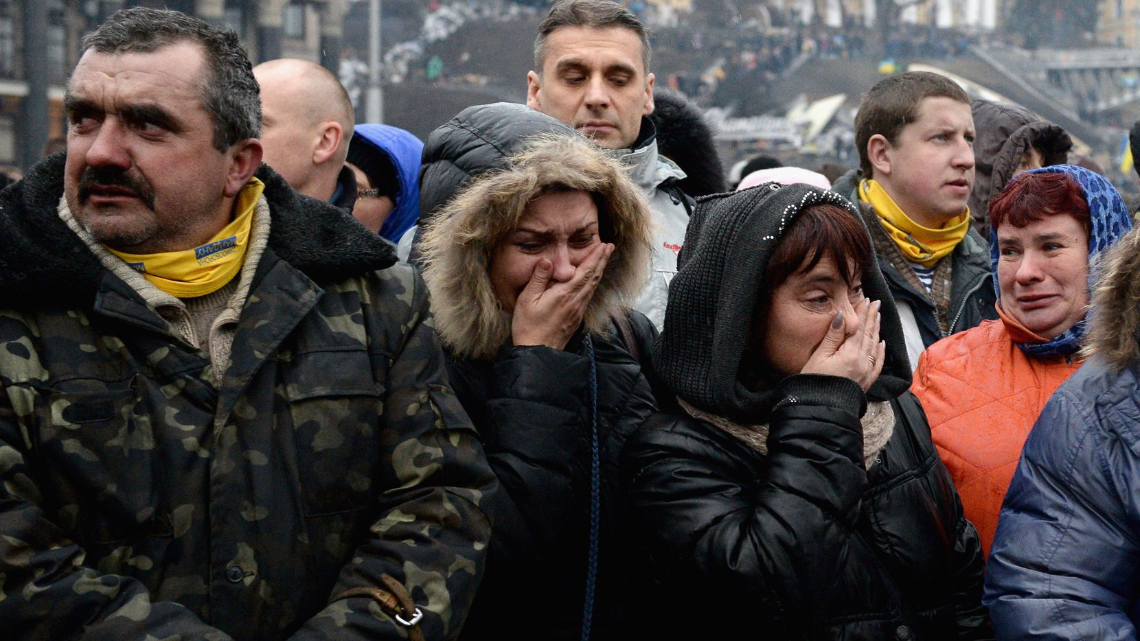 People react as the body of a dead anti-government demonstrator killed in clashes with police is carried through the crowd in Independence square in Kiev.