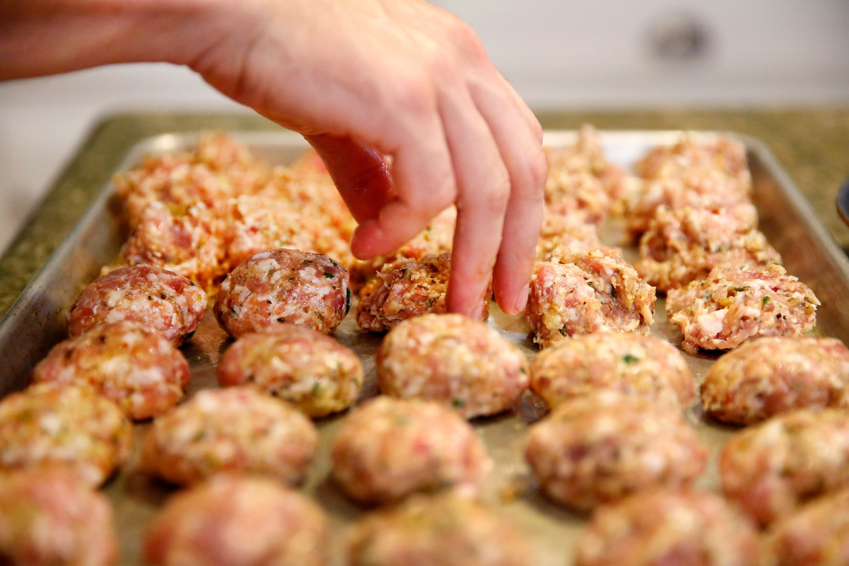 Restaurant owner and chef Julian Barsotti rolls rows of chicken thighs and pork belly meatballs in his hands as he prepares for the elaborate, multi-layered Italian dish known as a timpano at his Highland Park home. (Tom Fox/The Dallas Morning News)