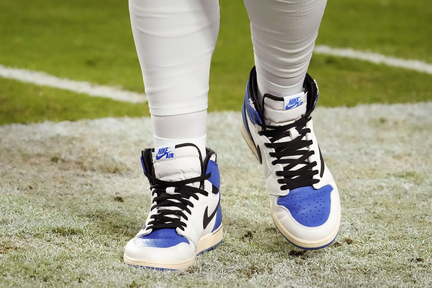 Dallas Cowboys quarterback Dak Prescott wears sneakers on the sidelines during the second half of a preseason NFL football game against the Arizona Cardinals at State Farm Stadium on Friday, Aug. 13, 2021, in Glendale, Ariz.