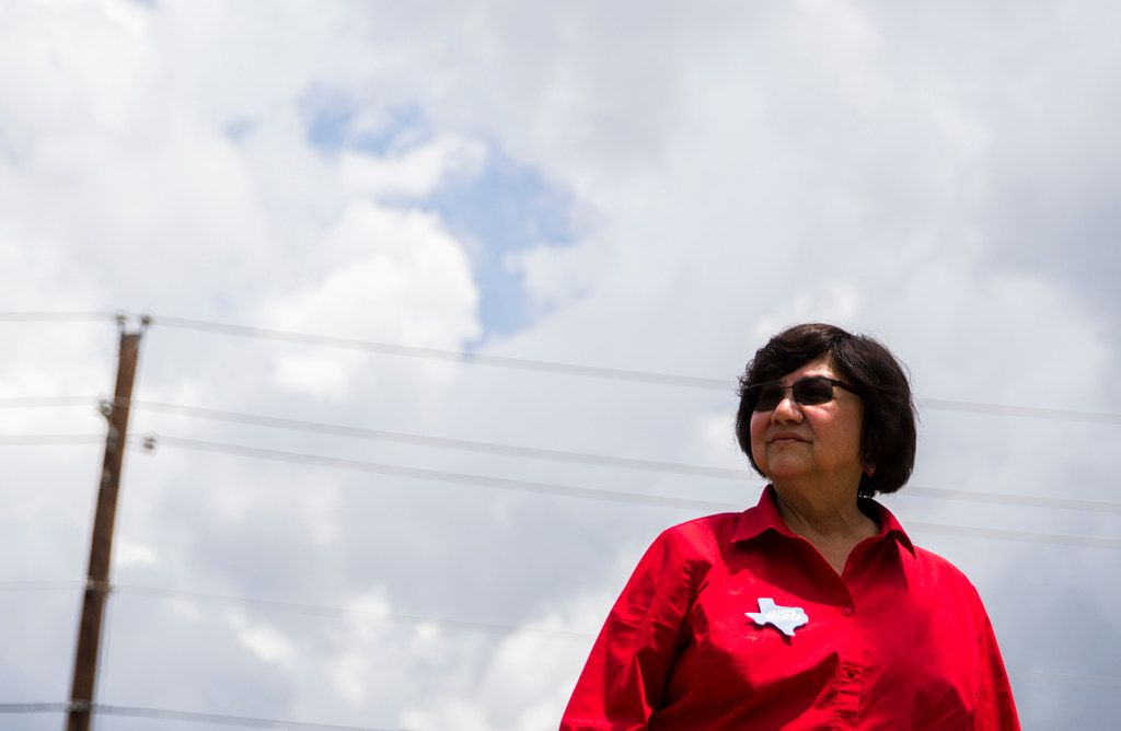 In this photo taken May 22, 2018, gubernatorial candidate and former Dallas County Sheriff Lupe Valdez waits to greet voters outside Renner Frankford Branch Library in Dallas.