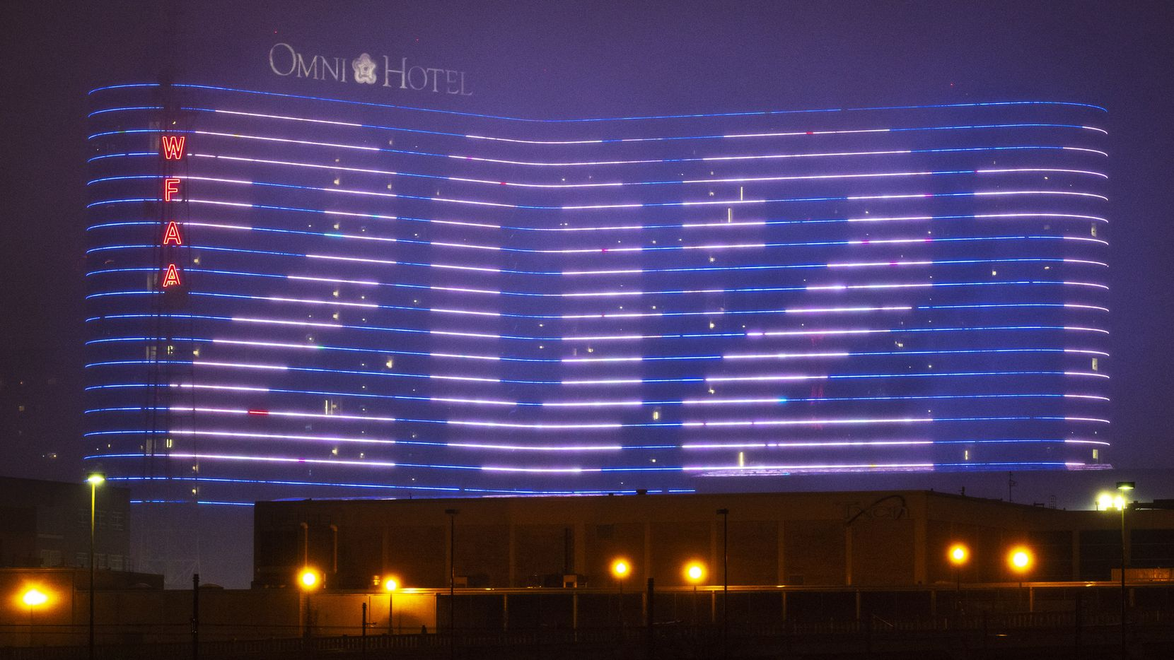 Through a light drizzle of rain and fog, Happy New Year 2021 was displayed on the electronic wall of the Omni Hotel in downtown Dallas after midnight Jan. 1. Hotels and other businesses in the leisure and hospitality industry have been hit harder than others by the pandemic.