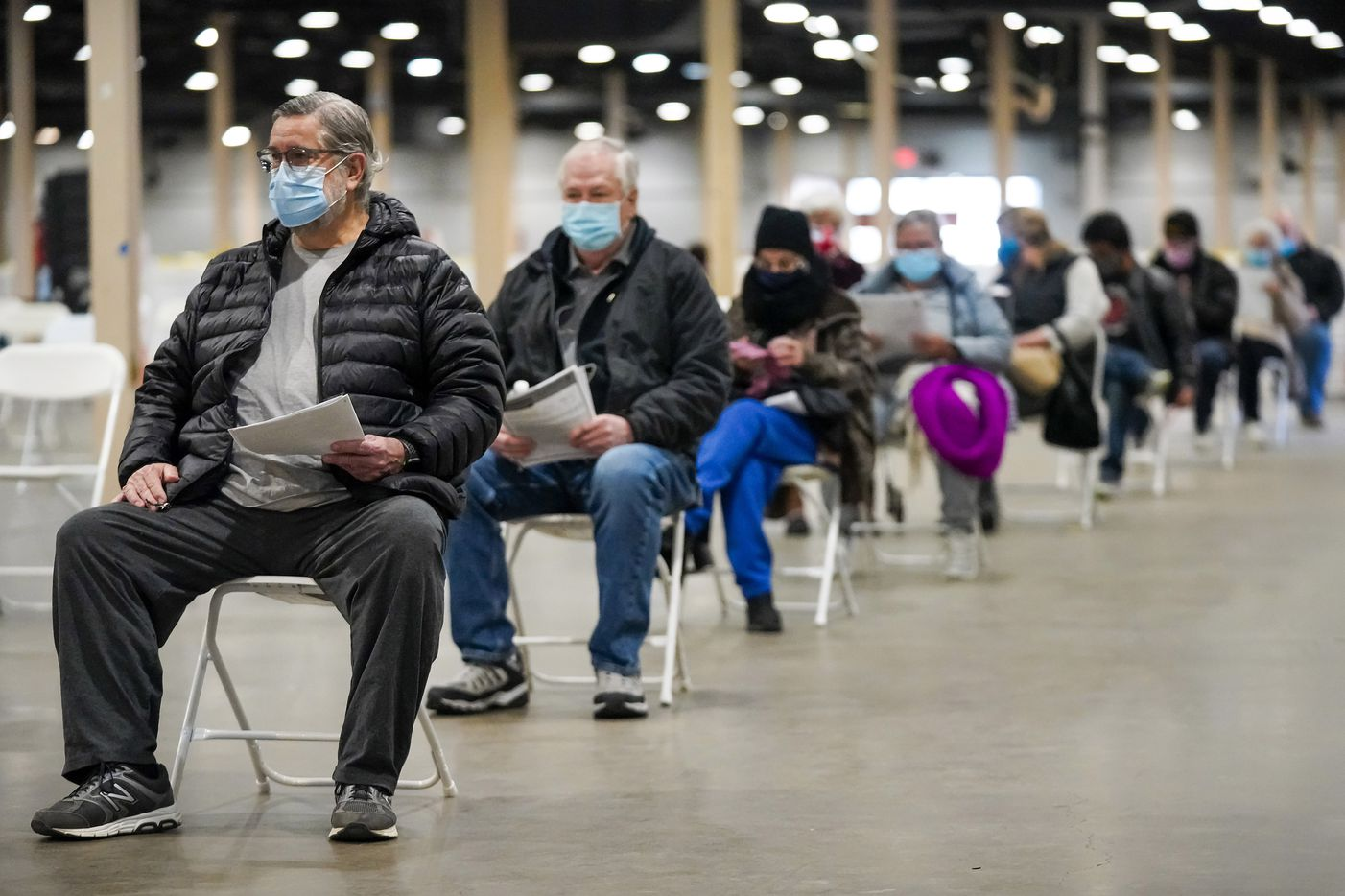 Davis Mosmeyer (left) waits at the front of the production line to receive the COVID-19 vaccine in Fair Park, Dallas on Monday, January 11, 2021. Dallas County launched its first