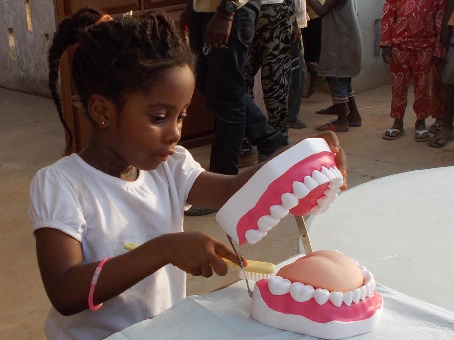 Eno Boateng of Ghana practices brushing teeth on a dental model in Elizabeth Acquaye-Kwarteng's traveling clinic.