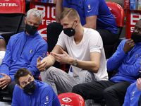 Injured Dallas Mavericks center Kristaps Porzingis (right) visits with coaches on the bench during their game with the Cleveland Cavaliers at the American Airlines Center in Dallas, Friday, May 7, 2021. The Mavericks blew out the Cavs, 110-90. (Tom Fox/The Dallas Morning News)