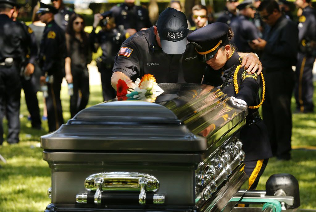 Millville (New Jersey) police chaplain Bob Ossler (left) is comforted by Dallas police Sr. Cpl. Margarita Argumedo of the police Honor Guard as they pray over the casket of slain Dallas police Sgt. Michael Smith as he is laid to rest at the Restland Funeral Home and Cemetery in Dallas, Thursday, July 14, 2016. Smith was gunned down in an ambush attack in downtown Dallas a week ago. Four Dallas police officers and one DART officer were killed. (Tom Fox/The Dallas Morning News)