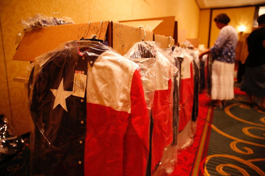 Gayle Sayers of Converse sorted Texas flag shirts donated by Houston insurance agent Norman Adams and his wife, Debbie, as Texas delegates to the Republican National Convention checked in for credentials Sunday.
